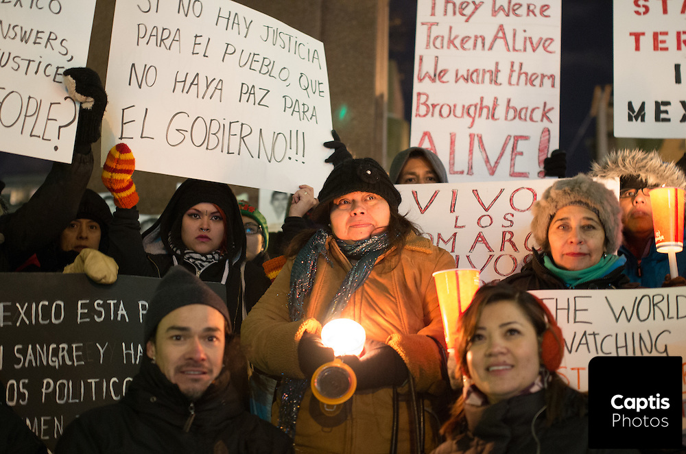 A group hold candles and protest signs as a candlelight vigil is held in Ottawa for the 43 missing Mexican students suspected to have been killed by a drugs gang. November 20, 2014.