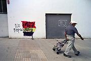 Spanje, El Ejido, 6-11-2019  Een man loopt langs een muur waar de spaanse vlag is gespoten. Er stond een leus in om van spanje een republiek te maken, tegen het koningshuis, monarchie,  maar koningsgezinden hebben het doorgestreept en een nieuwe leus tegen de republiek aangebracht .  In dit deel van Andalucie worden veel groente en fruit verbouwd die hun weg vinden via de export naar o.a. Nederland . Het wordt de zee van plastic genoemd omdat de kassen opgebouwd zijn van houten of metalen palen bedekt met zwaar plastic. Er kunnen soms vier oogsten per jaar gehaald worden. Het plastic kan ingeleverd worden bij een afvalbedrijf wat het recycled. Komende week zijn er algemene verkiezingen in Spanje en de populistische partij Vox heeft hier een grote aanhang. In de kassen werken voornamelijk migranten uit Afrika, en arbeidsmigranten uit Oost-Europa die een laag loon uitbetaald krijgen, tussen de 30 en 40 euro per 8 urige dag, werkdag, afhankelijk van de werkgever. Er wordt door de kaseigenaren en transportbedrijven goed verdiend maar de boeren vinden dat ze teveel negatieve aandacht krijgen in de media in noord-europa.Foto: Flip Franssen