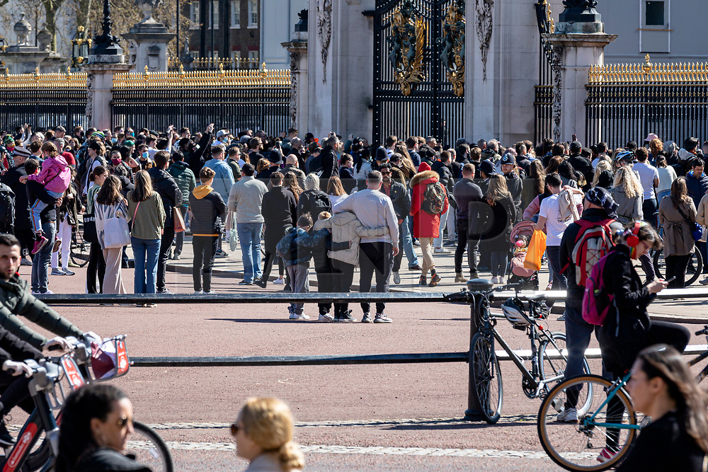 © Licensed to London News Pictures. 17/04/2021. London, UK. A family stand arm in arm as crowds gathered outside Buckingham Palace for the minute's silence as the funeral of The Duke of Edinburgh Prince Philip, Queen Elizabeth II's late husband, begins. The funeral is taking place in private at Windsor Castle. Photo credit: Rob Pinney/LNP