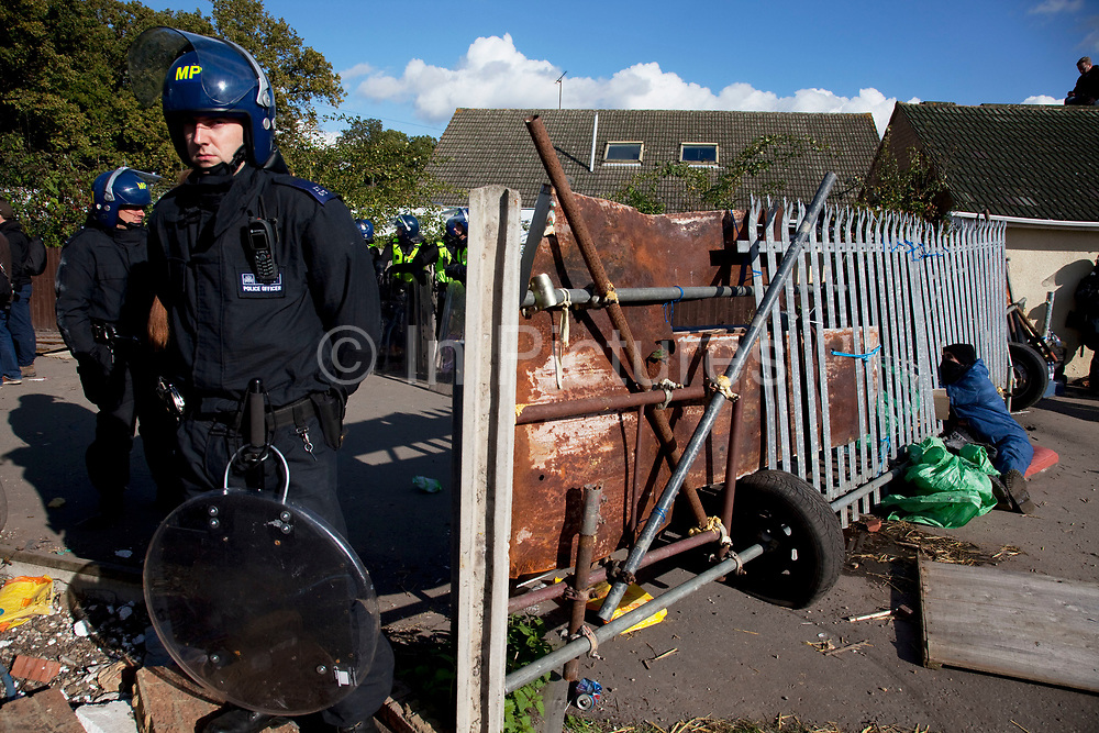 Aaron, a protester has his hands joined to another protester. Their hands are inside a barrell filled with concrete, bicycle locks and bars. Protesters who barricaded themselves above the entrance to the Dale Farm travellers' site have been removed by police as bailiffs prepare to move in. Essex Police cleared the scaffolding structure so it could be dismantled and machinery driven in by bailiffs to evict the travellers. On Wednesday night Essex Police said that over the course of the day 23 people had been arrested. Clearance of Dale Farm prior to eviction. Riot police and bailiffs were present on 19th October 2011, as a scaffolding gantry was cleared of protesters so the site could be cleared. Dale Farm is part of a Romany Gypsy and Irish Traveller site on Oak Lane in Crays Hill, Essex, United Kingdom. Dale Farm housed over 1,000 people, the largest Traveller concentration in the UK. The whole of the site is owned by residents and is located within the Green Belt. It is in two parts: in one, residents constructed buildings with planning permission to do so; in the other, residents were refused planning permission due to the green belt policy, and built on the site anyway.