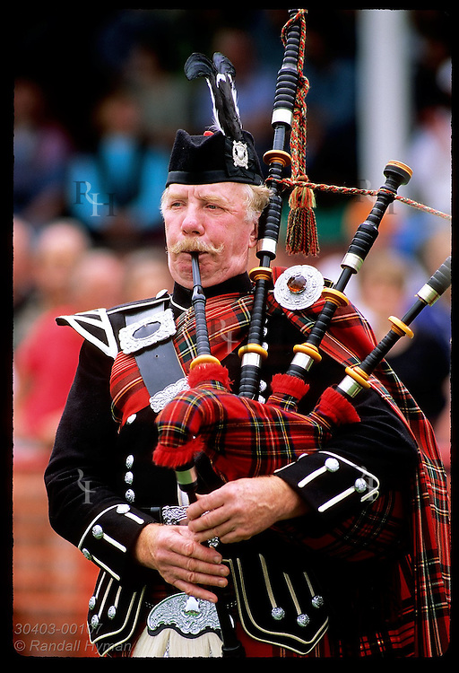 Moustached bagpiper blows on his pipes during performance at the Highland Games in Inverness. Scotland