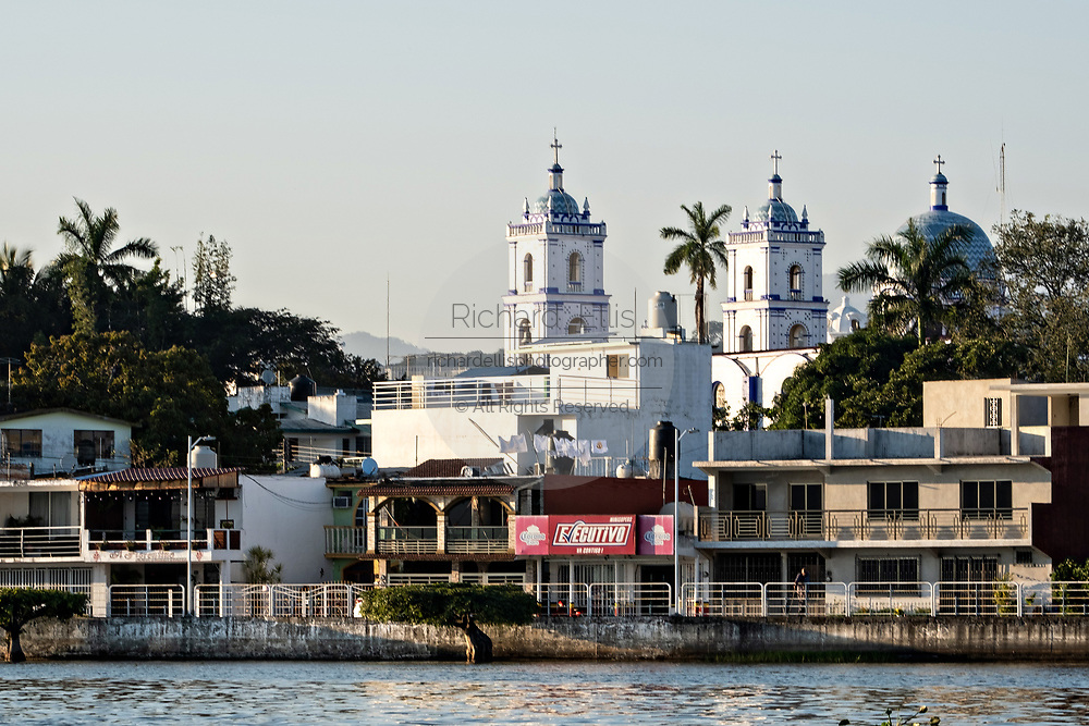 Waterfront view of Basilica of Our Lady of Mount Carmel and the along Lake Catemaco in Catemaco, Veracruz, Mexico. The tropical freshwater lake at the center of the Sierra de Los Tuxtlas mountains, is a popular tourist destination and known for free ranging monkeys, the rainforest backdrop and Mexican witches known as Brujos.