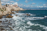 White foam rises from rolling waves on the Mediterranean Sea as they crash onto rocks below the seawall at Antibes, the French Riviera. Above the wall clouds float in a blue sky, and the city of Nice is seen in the background.
