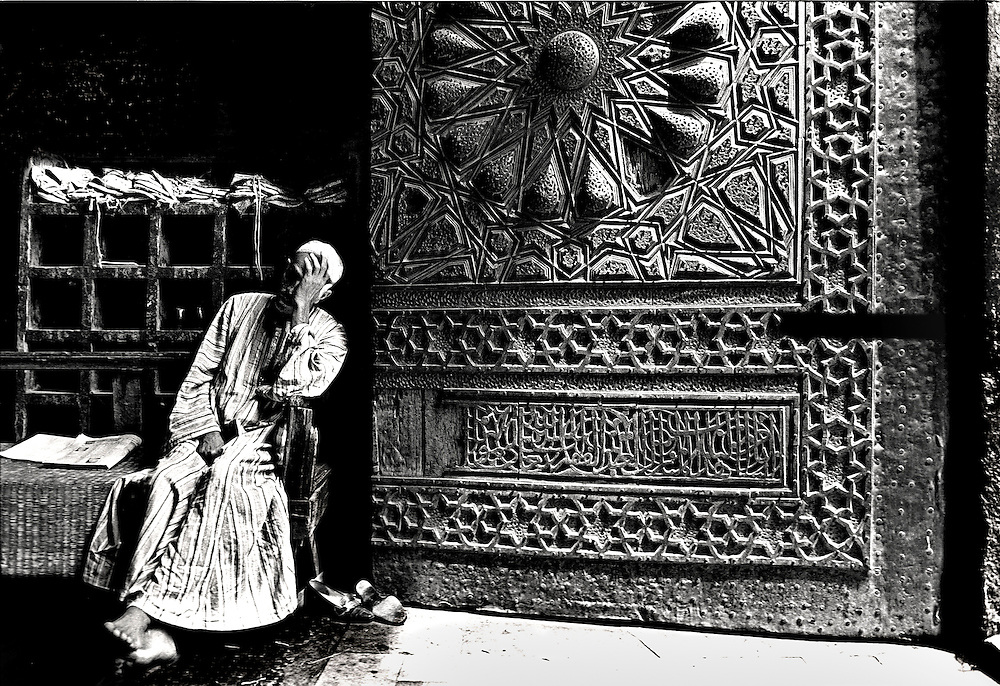 Doorway of the Mosque of the Sultan Al Mu'ayyad, (built 1415-1422) next to the Bab Zuweyla, Cairo; doorkeeper, seated with his shoes off, hand to his face.  He may be hiding from the camera, or he may be just resting or napping.   Door is heavily ornamented with repousse Islamic patterns.  Sunlight floods into the doorway.