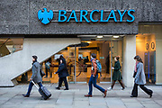 British pedestrians walk past a Barclays Bank in Moorgate, central London, United Kingdom.  Barclays PLC is a British multinational banking and financial service company headquartered in London, it is the seventh-largest worldwide bank.  The bank has been associated with many controversies including tax avoidance and large bonuses.