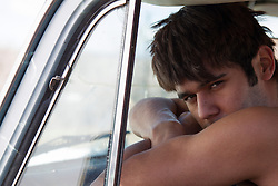 young man in sitting in a truck without a shirt