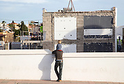 Child sitting on father's shoulders watching building site work, Fuerteventura, Canary Islands, Spain