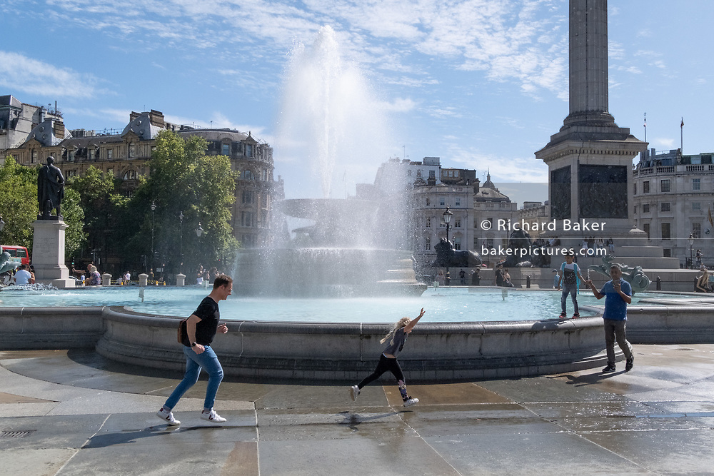 A young girl leaps in the air while running backwards and forwards through the spray from one of the fountains in Trafalgar Square, on 20th August 2020, in London, England