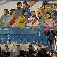 Haiti, Port-au-Prince, Woman sets up small market stall in front of Biblical mural along downtown street