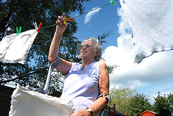 Elderly disabled women hangs her washing outside to dry; Leeds West Yorkshire
