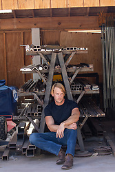 blond man in a black tee shirt and jeans