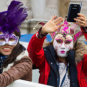 VENICE, ITALY - FEBRUARY 16: Tourists take pictures at the passage of the traditional regatta which officially opens the Venice Carnival  on February 16, 2014 in Venice, Italy. The 2014 Carnival of Venice will run from February 15 to March 4 and includes a program of gala dinners, parades, dances, masked balls and music events.  (Photo by Marco Secchi/Getty Images)