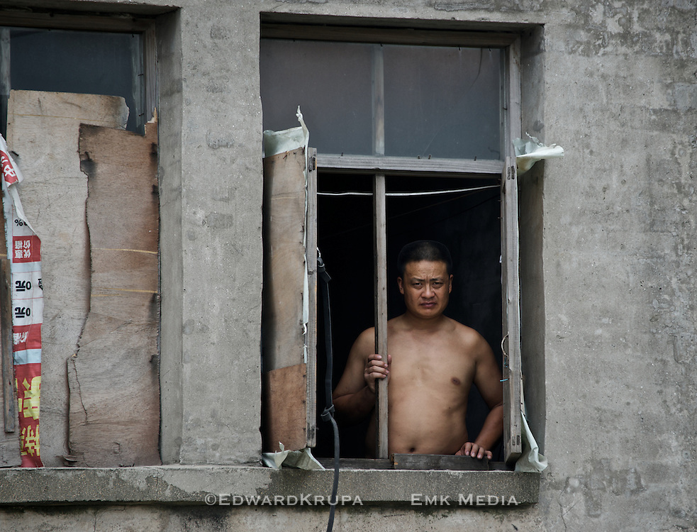 Man watching out of a window in rural village near the South China Sea.
