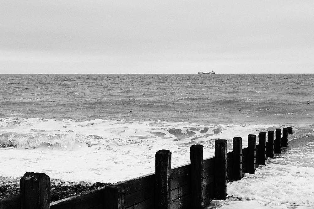 Boat on the horizon, waves crash on the beach on a windy morning in Cromer, North Norfolk.<br /> <br /> Photo by Jonathan J Fussell, COPYRIGHT 2021