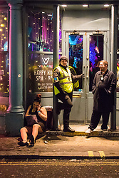 London, January 01 2018. A woman sits on the ground using her phone outside Village Bar on Wardour Street, Soho, as revellers in London's West End enjoy New Year's Eve. © SWNS