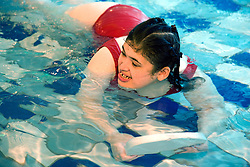 Day service users with learning disability swimming with a float at a local swimming pool,