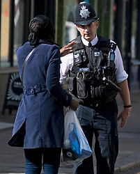 © Licensed to London News Pictures. 30/08/2020. London, UK. A Police officer talking to a local resident while patrolling  the streets of Notting Hill, West London, on the day of the 2020 Notting Hill Carnival which is bing held virtually this year due to COVID-19 restrictions. Members of the public have been warned against congregating in the Notting Hill Area to celebrate the event. Photo credit: Ben Cawthra/LNP