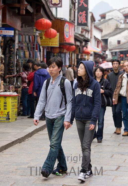 Couple walk down shopping street in Yangshuo, China