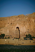 The cliff where once stood the Western Buddha (55m - 'Male') is photographed after sunset in Bamiyan, Afghanistan, an area mostly populated by Hazaras. The Buddhas of Bamiyan were two 6th century monumental statues of standing Buddhas carved into the side of a cliff in the Bamiyan valley in the Hazarajat region of central Afghanistan, situated 230 km northwest of Kabul at an altitude of 2500 meters. The statues represented the classic blended style of Gandhara art. The main bodies were hewn directly from the sandstone cliffs, but details were modelled in mud mixed with straw, coated with stucco. Amid widespread international condemnation, the smaller statues (55 and 39 meters respectively) were intentionally dynamited and destroyed in 2001 by the Taliban because they believed them to be un-Islamic idols. Once a stopping point along the Silk Road between China and the Middle East, researchers think Bamiyan was the site of monasteries housing as many as 5,000 monks during its peak as a Buddhist centre in the 6th and 7th centuries. It is now a UNESCO Heritage Site since 2003. Archaeologists from various countries across the world have been engaged in preservation, general maintenance around the site and renovation. Professor Tarzi, a notable An Afghan-born archaeologist from France, and a teacher in Strasbourg University, has been searching for a legendary 300m Sleeping Buddha statue in various sites between the original standing ones, as documented in the old account of a renowned Chinese scholar, Xuanzang, visiting the area in the 7th century. Professor Tarzi worked on projects to restore the other Bamiyan Buddhas in the late 1970s and has spent most of his career researching the existence of the missing giant Buddha in the valley.