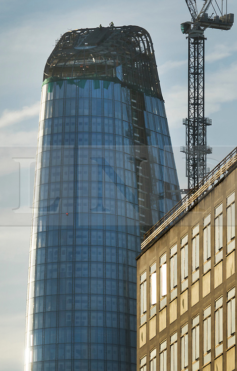 © Licensed to London News Pictures. 19/12/2017. London, UK. Construction workers brave the cold as they work at the top of the 'One Blackfriars' sky scraper next to the River THames, as parts of the UK are hit by fog and frost with travel disruption expected. The 52 storey appartment block began construction in 2013 and is 535 feet tall. Photo credit: Peter Macdiarmid/LNP
