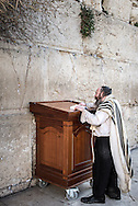 """A man in Tallit with visible tzitzit prays out loud at the Kotel in Jerusalem old city. Tzitzit is the name for specially knotted ritual fringes and are attached to the four corners of the tallit, as the Torah says """"You shall make yourself twisted threads, on the four corners of your garment with which you cover yourself"""".  While for man is natural to wear a shawls and pray out loud at the Western Wall, women can be arrested for doing so. Under Israeli law women are permitted to pray at the Western Wall, but only in silence. Ultra-Orthodox Jewish men say that women should not pray out loud in public because their voices are provocative. The activist group """"Women of the Wall' is engaged since 1988 in a campaign to win the right to perform the same rituals as men at Judaism's most religious site."""