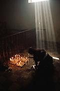 Gabriel Calixta praying and lighting candles in the cemetery chapel at Solola, Guatemala on Lake Atitlan.