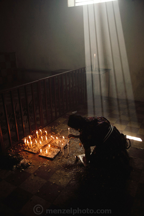 Gabriel Calixta praying and lighting candles in the cemetery chapel at Solola, Guatemala on Lake Atitlan.