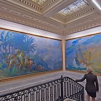Paintings of classic exploration overhang the stairs leading to the formal boardroom at the National Geographic headquarters in Washington, DC. (Anne Giesecke is walking down.)