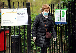 © Licensed to London News Pictures. 28/03/2020. London, UK. An elderly woman wearing a medical face mask walks past an NHS sign asking people to stay at home, at Paddington Recreation Ground in London, during a lockdown over the spread of COVID-19. Prime Minister Boris Johnson has announced that people should only leave their homes for essential work, groceries, medical necessity and exercise. Photo credit: Ben Cawthra/LNP