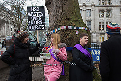 London, UK. 12th January, 2018. Anne Stevens (r), the vicar of St Pancras church, stands chained with local resident Jo Hurford (c) to a tree outside Euston station during a protest against the HS2 high-speed rail link. The protest formed part of a campaign by local residents against the planned felling of mature London Plane, Red Oak, Common Whitebeam, Common Lime and Wild Service trees in Euston Square Gardens to make way for temporary HS2 sites for construction vehicles and a displaced taxi rank.