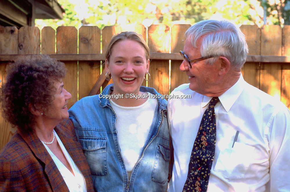 Granddaughter laughing with grandparents age 21 and 70.  St Paul Minnesota USA