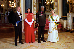 South African President Nelson Mandela, accompanied by his daughter Princess Zenani Mandela-Dlamini, stands with The Queen and Duke of Edinburgh in the Music Room of Buckingham Palace before a state banquet in the president's honour.