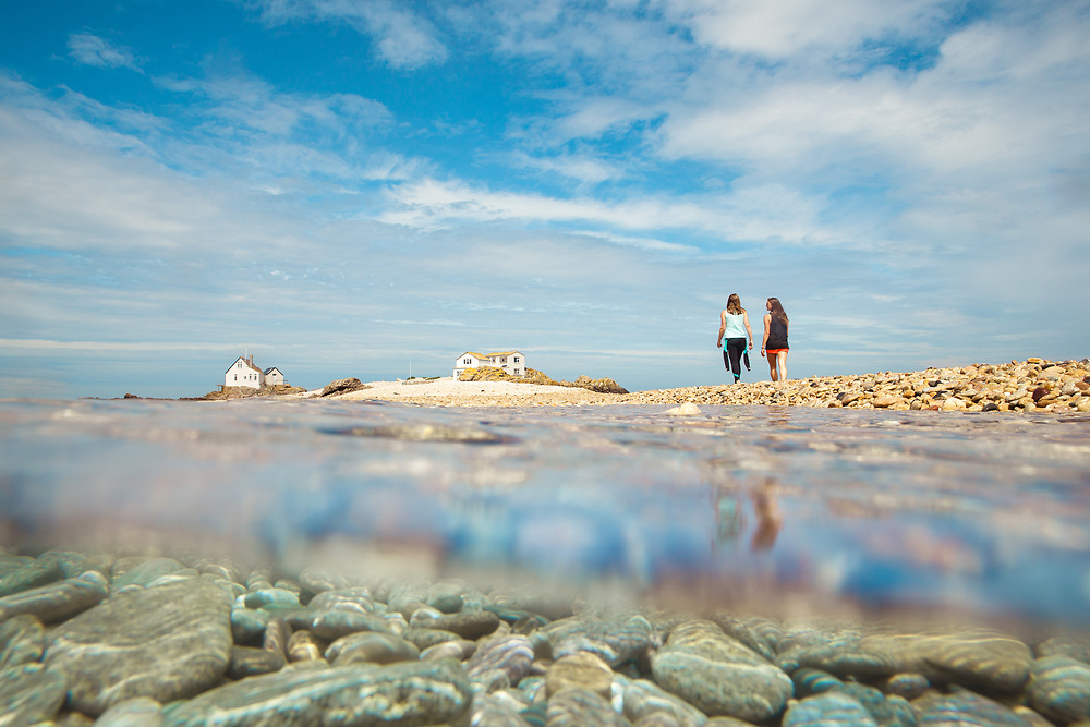 View of people walking along the pebble beach at the Ecrehous from half underwater