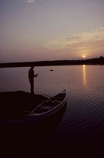 Boundary Waters Canoe Area, Ontario's Quetico Provincial Park, sunrise on Koma Lake. Fisherman casts from shore. Summer.