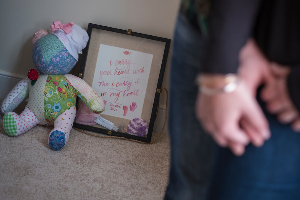 """Fredericksburg, VA  - Lindsey and Matt Paradiso, photographed inside their home, March 12, 2017 in downtown Fredericksburg, Virginia.  Lindsey, 28 years old, and Matt, 31 years old, talk about their pregnancy and subsequent """"late term abortion"""" due to medical complications. Omara Rose, the name the chose for their daughter, was aborted at 25 weeks, February 26, 2016. A shadow box of memories of their daughter including their daughters hand and foot prints sits with teddy bear while the couple holds hands. Photo Justin Ide"""