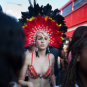 A young white woman dressed only in her skimpy red dance outfit and feathers makes her way through the crowd.  The Notting Hill Carnival has been running since 1966 and is every year attended by up to a million people. The carnival is a mix of amazing dance parades and street parties with a distinct Caribbean feel.