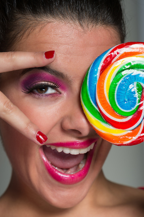 Happy and smiling girl with huge colorful lollipop