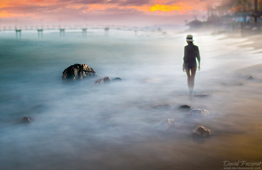 Woman walking on the shore of a dreamy beach.