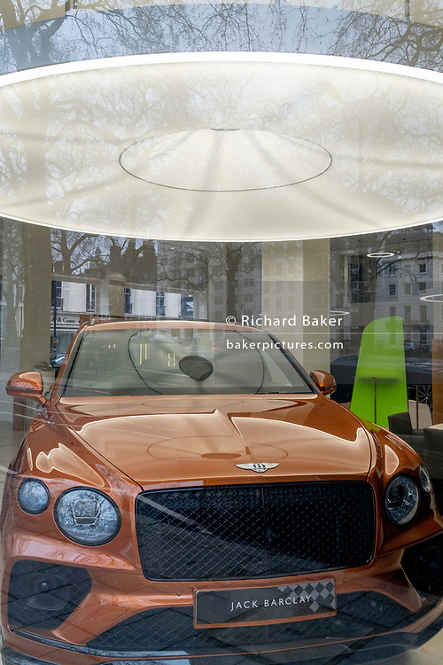 Seen through a window during the closure of non-essential businesses during the Coronavirus pandemic, a luxury Bentley car is in the Jack Barclay showroom in Mayfair,  on 4th March 2021, in London, England.