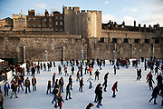 London, UK. Saturday 8th December 2012. People ice skating at London's open-air ice rink at the Tower of London. The ice rink is set against the magnificent fortress battlements, providing a stunning setting for winter skating in the City.