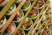 "Meat salads are stacked in readiness for an airline flight in the world's largest independent provider of airline catering and provisioning services, Gate Gourmet, on the southern perimeter road at Heathrow Airport, West London. Gate Gourmet serve more than 200 million meals on 2 million airline flights a year to their 250-plus airline customers at more than 100 airport locations around the globe. Apart from creating the bespoke meals for an airline's culture and ethnic demands, that pack the pre-flight carts, deliver and load into the aircraft galleys and afterwards, they dispose of the waste and strip, wash and sterilize the equipment. From writer Alain de Botton's book project ""A Week at the Airport: A Heathrow Diary"" (2009)."