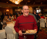 Norman Richard with a plate of lollipop chicken from Contigiani's and Hermitage wine from Hermit Woods Winery during the 26th annual Altrusa Taste of the Lakes Region event at Church Landing on Sunday evening.  (Karen Bobotas/for the Laconia Daily Sun)