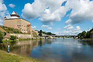 Narva, Estonia - July 24, 2015: A man fishes in the Narva River in Narva, Estonia. On the left is Hermann Castle, first built by the Danes in the 13th century. The bridge over the river connects Narva with the Russian city of Ivangorod.