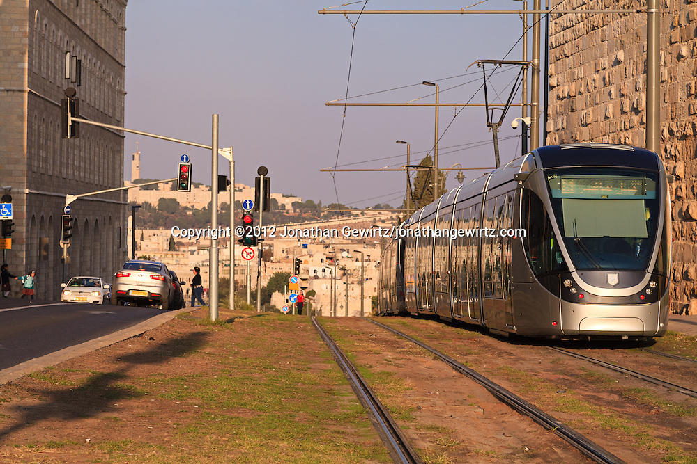 A train in Jerusalem's light rail system travels down Sultan Suleiman Street along the walls of the Old City of Jerusalem. Mount Scopus is visible in the distant background. WATERMARKS WILL NOT APPEAR ON PRINTS OR LICENSED IMAGES.