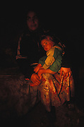 Roma mother and child, shelter from a harsh winter, keeping warm next to a wood burning stove, in their hovel. Timisoara, Romania Winter 2004