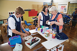 Staff at special school preparing a snack for children with physical and learning disabilities,