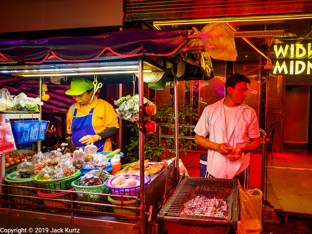 """27 FEBRUARY 2019 - BANGKOK, THAILAND: A street food stall that caters to workers on Soi Cowboy, one of Bangkok's """"adult entertainment"""" districts waits for customers. Bangkok, a city of about 14 million, is famous for its raucous nightlife. But Bangkok's real nightlife is seen in its markets and street stalls, many of which are open through the night.         PHOTO BY JACK KURTZ"""