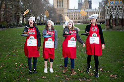 © Licensed to London News Pictures. 13/02/2018. London, UK. Liz Bates, Georgie Prodromue, Rachael Venables and Laura Hughes of the Media team practise ahead of the Rehab Parliamentary Pancake Race 2018 in Victoria Tower Gardens. The Parliament Team - made up of MPs, Lords and Ladies - race in a relay against the Media Team - made up of reporters and presenters - whilst continuously flipping pancakes to celebrate Shrove Tuesday, also known as Pancake Day. Photo credit : Tom Nicholson/LNP