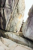 Woman standing amid granite walls and boulders&#xA;<br />