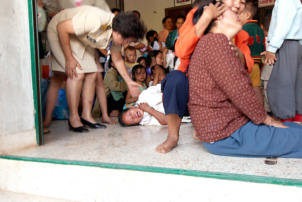 """There were tense scenes at the Nong Khai Immigration Detention Center as authorities tried to deport 152 Hmong refugees back to Laos, Nong Khai, Thailand, on Tuesday January 30th, 2007.  In protest the women and children sat in the street infront of the buses.  Some Hmong collapsed with emotion and exhaustion from the ordeal.  ..The deportation was postponed after the Hmong men barricaded their jail cell and threatened mass suicide if they were forcibly sent back to Laos where they face possible torture and death.  ..The men reportedly declared, """"We would rather die in Thailand than be sent back to Laos"""".  ..On May 16, 2007 the Thai Military Junta forced the UNHCR Bangkok refugee office to stop accepting applications from asylum seekers.  On Friday night June 8, 2007, after UNHCR and western diplomats had gone home for the weekend, Thai authorities forcibly deported a different group of 160 Hmong asylum seekers to back Laos...Up to 1,000 Hmong jungle people surrendered to Lao authorities last year due to Lao Military pressure, an inability to defend themselves, and lack of food or medicine.   This includes Blia Shoua Her's group of 438 people who suffered the massacre April 6, 2006.  All of these Hmong have vanished and the Lao Government has made no account of their whereabouts or condition despite requests from humanitarian groups."""